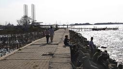 Warga menikmati suasana sore di Pantai Marunda, Teluk Jakarta, Selasa (11/9). Pantai Marunda menjadi tempat alternatif berlibur keluarga dan menghibur diri dengan memancing di bibir pantai tersebut. (Merdeka.com/Imam Buhori)