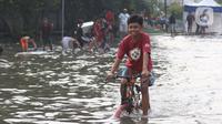 Seorang anak bermain sepeda di genangan air akibat banjir rob di kawasan pintu masuk Pelabuhan Nizam Zachman, Muara Baru, Jakarta, Jumat (5/6/2020). Banjir rob di Pelabuhan Muara Baru tersebut terjadi akibat cuaca ekstrem serta pasang air laut. (Liputan6.com/Helmi Fithriansyah)