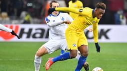 Aksi Hodson-Odoi melewati Nicholas Shaparenko pada leg kedua, babak 16 besar Liga Europa yang berlangsung di Stadion Stamford Bridge, London, Jumat (15/3). Chelsea menang 5-0 atas Dynamo Kiev. (AFP/Sergei Supinski)