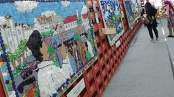 Pengunjung melihat-lihat karya seni instalasi dari bahan bekas pakai yang dipamerkan terowongan Jalan Kendal, Jakarta, Selasa (20/8/2019). Pemeran seni instalasi ini bertajuk Kenali Sejarah Perkeretapianmu dengan konsep Eco Living Go Green. (Liputan6.com/Helmi Fithriansyah)