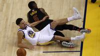 Guard Golden State Warriors Klay Thompson (bawah) terkena cedera setelah berbenturan dengan  JR Smith pada laga pertama final NBA. (AFP/Ezra Shaw)