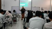 Seorang dosen IPB, Arif Satria sedang mengajar dengan mengenakan pakaian adat Bali, Senin (28/10/2019). (Liputan6.com/Achmad Sudarno)