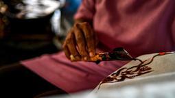 Seorang pekerja membuat desain batik di sebuah bengkel di Banda Aceh, Aceh, Rabu (13/10/2021). Pemilihan warna membuat kain batik Aceh terlihat cerah dan juga glamor. (Chaideer MAHYUDDIN/AFP)