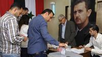 Penduduk Suriah menggunakan haknya untuk memilih di tempat pemungutan suara, guna menyambut pemilu lokal. (Kantor Berita SANA via AP)