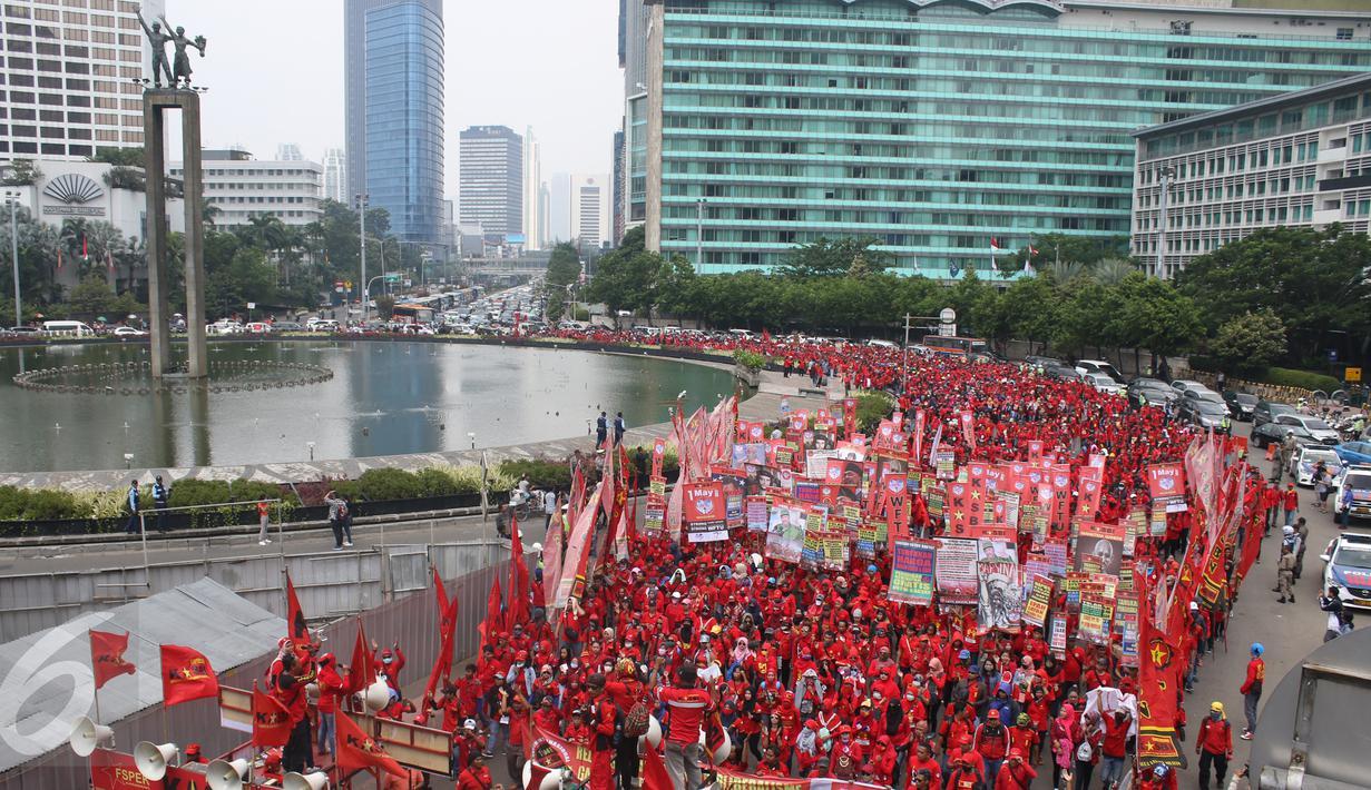 Buruh Konfederasi Kongres Aliansi Serikat Buruh Indonesia (Kasbi) menggelar aksi peringatan May Day di Bundaran HI, Jakarta, Senin (1/5). Massa buruh dari berbagai daerah itu akan menyuarakan tuntutan di depan Istana Presiden. (Liputan6.com/Angga Yuniar)
