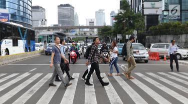 Warga menyebrang jalan Sudirman di kawasan Tosari, Jakarta, Jumat (14/12). Penggunaan pelican crossing di kawasan ini menggantikan fungsi Jembatan Penyebrangan Orang (JPO) Tosari yang akan dibongkar. (Liputan6.com/Helmi Fithriansyah)