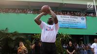Pemain NBA dari Boston Celtics, Jaylen Brown memberi melempat bola basket saat coaching clinics untuk siswa-siswi di SMAN 82 Jakarta, Kamis (26/7). Kegiatan tersebut untuk memperkenalkan olahraga basket bagi anak-anak. (Liputan6.com/Arya Manggala)