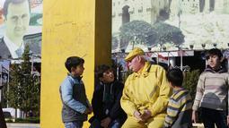 Abu Zakkour yang dijuluki 'Yellow Man' bersama anak-anak di alun-alun pusat Saadallah al-Jabiri, Suriah utara pada 11 Februari 2019. Abou Zakkour memutuskan hanya mengenakan  segala sesuatu yang berwarna kuning, termasuk jas, kemeja, kaus kaki, sepatu, dan kacamata. (LOUAI BESHARA/AFP)