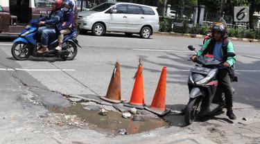 Pengendara menghindari jalan berlubang di kawasan Tanjung Barat, Jakarta, Rabu (30/1). Musim penghujan, pengguna jalan mengeluhkan jalan berlubang yang dipenuhi air.  (Liputan6.com/Immanuel Antonius)