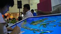 Seorang pengunjung pameran wisata MITM sedang mencari destinasi wisata Indonesia menggunakan peta interaktif.