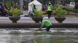 Petugas membersihkan busa yang mencemari kolam air mancur di bundaran patung kuda, Jakarta, Rabu (28/3). Petugas masih menyelidiki asal busa tersebut. (Liputan6.com/Arya Manggala)