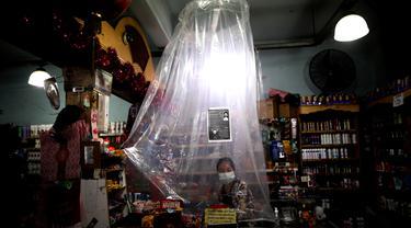 Kasir supermarket menunggu pelanggan di balik tirai plastik darurat di Buenos Aires, Argentina pada 16 Maret 2020. Kasir supermarket tersebut memakai pembatas plastik untuk membuat sekat dengan pembeli guna mencegah penyebaran virus corona Covid-19. (AP/Natacha Pisarenko)