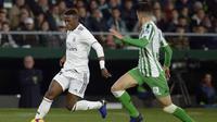 Vinicius jr mencoba melewati hadangan pemain Real Betis pada laga lanjutan La Liga Spanyol yang berlangsung di stadion Benito Villamarin, Senin (14/1). Real Madrid menang 2-1 atas Real Betis. (AFP/Cristina Quicler)