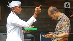 Pemuka agama memercikkan air suci di Pura Aditya Jaya di Jakarta, Selasa (24/3/2020). Ibadah hari suci Nyepi Tahun Baru Saka 1942 di Pura Aditya Jaya tidak menyelenggarakan persembahyangan, namun untuk sembahyang dibatasi dalam mencegah penularan Covid-19. (Liputan6.com/Herman Zakharia)