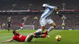 Pemain Manchester United, Juan Mata menghalau bola dari kaki pemain Huddersfield Town, Collin Quaner pada laga Premier League di Old Trafford, Manchester, (3/2/2018). MU menang 2-0. (Martin Rickett/PA via AP)