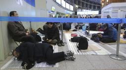 Seorang pria tidur ketika dia menunggu untuk membeli tiket kereta api untuk mudik ke kota asalnya selama liburan Tahun Baru Imlek, di Stasiun Kereta Api Seoul di Seoul, Korea Selatan, Selasa (7/1/2020). Tahun Baru Imlek jatuh pada 25 Januari tahun ini. (AP Photo/Ahn Young-joon)