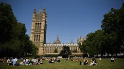 Orang-orang berbincang saat bersantai di bawah sinar matahari di Victoria Tower Gardens dekat Gedung Parlemen di London (23/7/2019). Suhu melonjak di atas 30C (86F) di Inggris pada 23 Juli dengan para peramal cuaca memperkirakan suhu setinggi 37C (96.8F) sebelum akhir pekan. (AFP Photo/Ben Stansall)