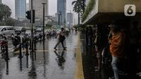 Aktivitas warga saat hujan mengguyur kawasan Jakarta, Selasa (16/2/2021). Sebagai tahap awal vaksinasi COVID-19 tahap kedua bagi pekerja publik akan dimulai dari para pedagang Pasar Tanah Abang pada Rabu 17 Februari 2021. (Liputan6.com/Johan Tallo)