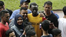 Pemain Arema FC, Makan Konate, foto bersama dengan fans usai sesi latihan di Stadion Gajayana, Malang, Kamis (11/4). Setelah sesi latihan, pemain Arema FC melayani permintaan fans untuk foto bersama. (Bola.com/Yoppy Renato)