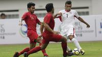 Gelandang Yordania, Omar Hani Ismail, berusaha melewati pemain Indonesia pada laga persahabatan di Stadion Wibawa Mukti, Jawa Barat,  Sabtu (13/10/2018). Indonesia menang 3-2 atas Yordania. (Bola.com/M Iqbal Ichsan)