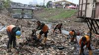Petugas membersihkan sampah yang memenuhi aliran Kali Gendong di kawasan Penjaringan, Jakarta, Senin (3/12). Penumpukan sampah diperparah dengan perilaku warga yang membuang sampah sembarangan. (Liputan6.com/Immanuel Antonius)