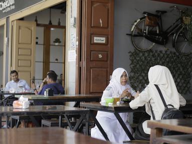 Pengunjung duduk di sebuah restoran di Bireuen, Aceh, Rabu (5/9). Pemerintah Kabupaten Bireuen mengharamkan perempuan dan lelaki yang nonmuhrim minum kopi semeja di restoran, kafe, bahkan di warung kopi biasa. (AFP PHOTO/AMANDA JUFRIAN)