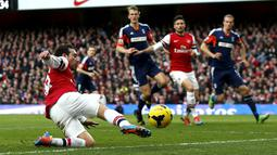 Santi Cazorla berusaha menggapai Bola pada pertandingan sepak bola Liga Inggris antara Arsenal vs Fulham di Stadion Emirates, London (18/01/14). (AFP/Adrian Dennis)
