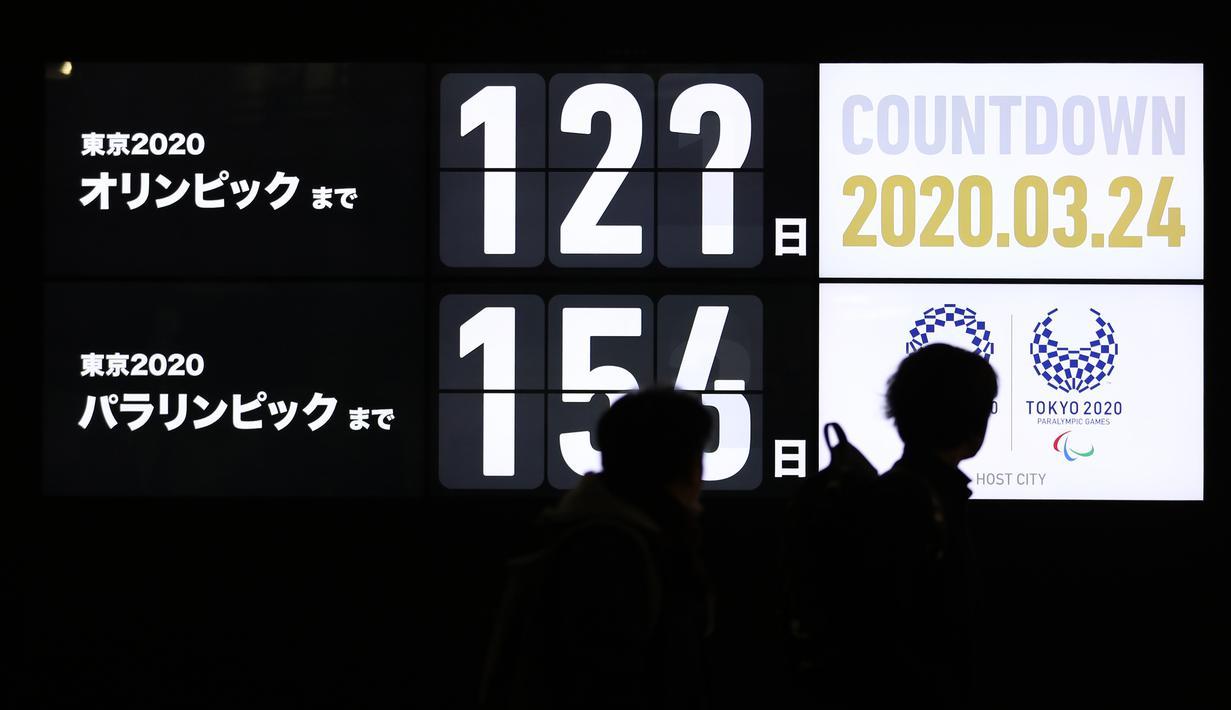 Pejalan kaki melintasi layar hitung mundur untuk Olimpiade Tokyo 2020 di Distrik Shimbashi di Tokyo, 24 Maret 2020. PM Jepang Shinzo Abe mengumumkan Jepang dan Komite Olimpiade Internasional (IOC) telah sepakat untuk menunda gelaran Olimpiade dan Paralimpiade Tokyo hingga setahun. (Xinhua/Du Xiaoyi)