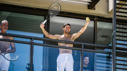 Petenis pria peringkat satu dunia, Novak Djokovic menyapa penggemarnya disela-sela menjalani latihan dari balkon hotel, Adelaide, Australia, Rabu (20/1/2021). (Foto: AFP/Morgan Sette)