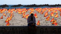Seorang pria duduk di dekat ribuan bendera Spanyol yang mewakili korban COVID-19 di negara itu dipasang di pantai Patacona, Valencia pada Minggu (4/10/2020). Virus corona di Spanyol sejauh ini telah merenggut lebih dari 32.000 nyawa dan 790.000 kasus terkonfirmasi. (Jose Jordan / AFP)