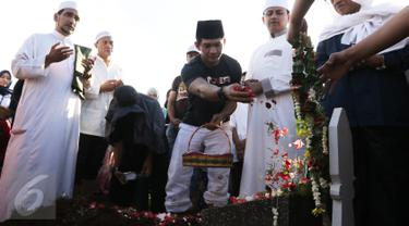 Aktor Iko Uwais menaburkan bunga di pemakaman ayahnya Musthafa Kamaluddin di TPU Prumpung, Jakarta, Rabu (8/3). Ayah Iko Uwais wafat pada  Rabu (8/3/2017) pagi di RSCM. (Liputan6.com/Herman Zakharia)