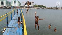 Sejumlah anak melompat saat bermain air dekat tanggul laut Muara Baru di Penjaringan, Jakarta Utara, Minggu (1/9/2019). Anak-anak memanfaatkan sisi tanggul laut raksasa (giant sea wall) sebagai   tempat  bermain alternatif. (merdeka.com/Arie Basuki)