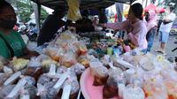 Penjual melayani pembeli makanan untuk berbuka puasa (takjil) di kawasan Pasar Lama, Kota Tangerang, Selasa (20/4/2021). Bulan Ramadhan, membuat sejumlah pedagang takjil musiman bermunculan dan menawarkan aneka makanan dan minuman untuk umat Islam yang menjalankan puasa. (Liputan6.com/Angga Yuniar)