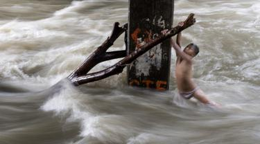 Seorang bocah laki-laki memegang batang pohon saat ia bermain di sungai dengan arus yang sangat deras akibat hujan lebat di bawah jembatan di Manila, Filipina (11/6). (AFP Photo/Noel Celis)