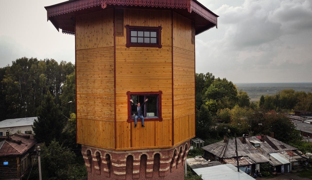 Pengusaha Rusia Alexander Lunev duduk di jendela bekas menara air, yang diubah menjadi apartemen, di kota Tomsk, Siberia pada 7 September 2020. Alexander Lunev, mantan presenter radio dari Kota Tomsk telah membeli menara air berusia 125 tahun dari kotamadya pada tahun 2012. (Alexander NEMENOV / AFP)
