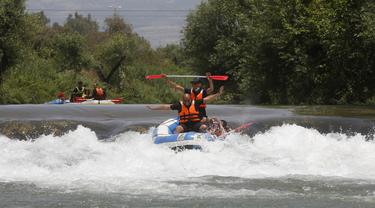 Umat muslim merayakan liburan Idul Fitri dengan rafting menyusuri Sungai Hasbani, Anak Sungai Yordan, di Kfar Blum, Israel, Rabu (27/5/2020). Pemerintah Israel mengurangi pembatasan aktivitas terkait pandemi virus corona COVID-19. (JALAA MAREY/AFP)
