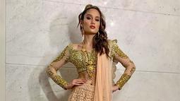 Cinta Laura tampil glamour dalam pakaian crop top berwarna emas dipadukan dengan rok panjang kombinasi warna krem dan emas. Tak lupa, kain panjang dan aksesoris yang berwarna senada. (Liputan6.com/IG/@claurakiehl)