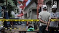 Pekerja berjaga di dekat garis polisi usai ambruknya crane pengerjaan proyek double-double track kereta api di Jatinegara, Jakarta, Minggu (4/2). (Liputan6.com/Faizal Fanani)