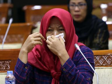 Terpidana kasus pelanggaran UU ITE sekaligus korban pelecehan seksual Baiq Nuril menangis saat hadir dalam rapat pleno Komisi III DPR di Gedung Nusantara III, Jakarta, Rabu (23/7/2019). Rapat membahas surat pertimbangan amnesti dari Presiden Joko Widodo. (Liputan6.com/JohanTallo)