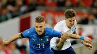 Pemain timnas Italia, Ciro Immobile berebut bola dengan pemain timnas Inggris, John Stone dalam laga persahabatan di Stadion Wembley, Rabu (28/3).  Sempat tertinggal, Italia menahan imbang Inggris 1-1. (AP Photo/Alastair Grant)