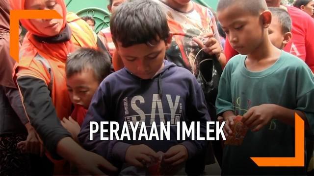 Puluhan masyarakat Pademangan Jakarta Utara menunggu pembagian Ang Pao dari warga Tionghoa yang merayakan Imlek. Pembahgian Ang Pao dikwal anggota Polsek pademangan Jakarta Utara