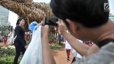 """Pengunjung Car Free Day berfoto dengan latar belakang instalasi bambu """"Getih Getah"""" di Bundaran HI, Jakarta, Minggu (19/8). Karya seni Joko Avianto itu langsung diserbu dan menjadi objek foto baru bagi sejumlah masyarakat. (Merdeka.com/ Iqbal S. Nugroho)"""