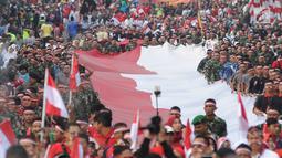 Anggota TNI POLRI  bersama warga masyarakat membawa bendera raksasa berukuran panjang 117 meter dan lebar 5 meter saat gelaran Festival Merah-Putih (FMP) 2018 di kawasan Air Mancur, Bogor ,  Minggu (5/8). (Merdeka.com/Arie Basuki)