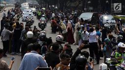 Iring-iringan mobil jenazah yang membawa almarhum Presiden ke-3 RI, BJ Habibie melintasi Jalan Gatot Subroto menuju TMP Kalibata, Jakarta, Kamis (12/9/2019). Warga secara khusus meluangkan waktu menyambut jenazah BJ Habibie untuk memberikan penghormatan terakhir. (Liputan6.com/Johan Tallo)