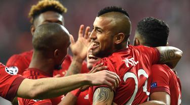 Pemain Bayern Munchen, Arturo Vidal, disambut rekan-rekannya setelah mencetak gol ke gawang Benfica pada leg pertama babak perempat final Liga Champions di Allianz Arena, Munchen, Rabu (6/4/2016) dini hari WIB. (AFP/Christof Stache)