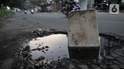 Tong sampah untuk menutupi jalan berlubang di Jalan Tegar Beriman, Cibinong, Bogor, Minggu (31/5/2020). Sudah berbulan-bulan akses yang dikenal sebagai jalan Pemda Cibinong ini sangat memprihatinkan hingga sering menyebabkan kecelakaan terlebih saat musim hujan. (merdeka.com/Iqbal Nugroho)