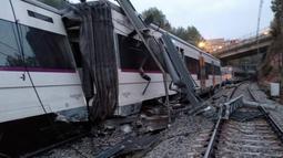 Sebuah kereta komuter yang tergelincir dan keluar jalur  akibat terjangan longsor di Vacarisses, Barcelona, Selasa (20/11). Diketahui ada sekitar 150 penumpang di dalam kereta saat kecelakaan tersebut. (Anti-radar Catalunya via AP)