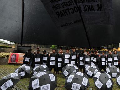 Sejumlah aktivis dari Gema Tapteng berbaris melakukan aksi teatrikal saat melakukan aksi unjuk rasa di depan gedung KPK, Jakarta, Kamis (26/4). Mereka menutut pimpinan KPK untuk mengusut tuntas Bakhtiar Ahmad Sibarani. (Merdeka.com/Dwi Narwoko)