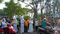 Petugas yang mengenakan pakaian mirip pocong dihadirkan saat razia masker di jalan protokol dan pasar tradisional di Kota Bekasi, Rabu (16/9/2020). (Liputan6.com/Bam Sinulingga)