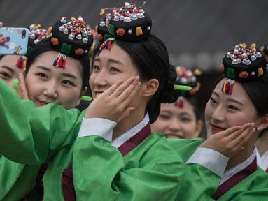 Pelajar berswafoto sambil mengenakan kostum tradisional Korea Selatan (Korsel) setelah upacara Coming of Age Day di Namsan Hanok Village, Seoul, Senin (15/5). Coming of age day atau Hari Kedewasaan dirayakan pada minggu ketiga bulan Mei. (Ed JONES/AFP)